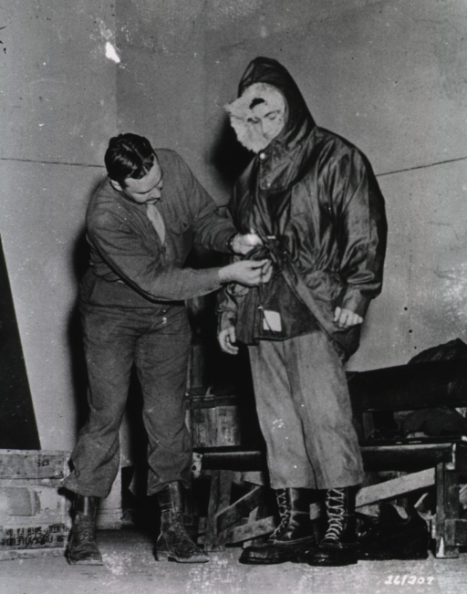 <p>Lt. Lee stands, wearing an oversized parka, heavy pants, and army boots, while another man in military uniform fastens the parka.</p>