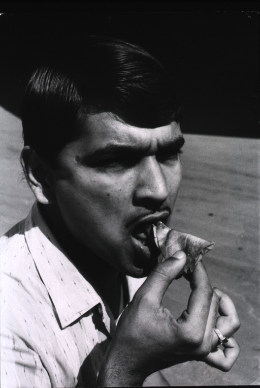 <p>A man is placing betel quid into his mouth.</p>