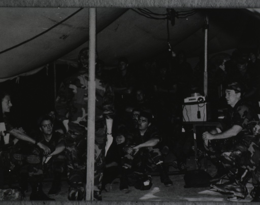 <p>A group of men in uniforms inside a tent.</p>