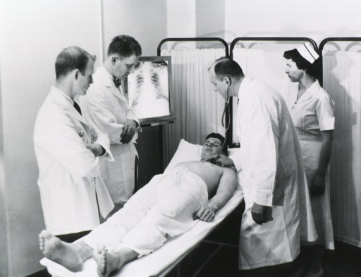 <p>Interior view: a patient is lying on a cot in an examination area; Terry (shown in left profile) is listening to the patient's chest with a stethoscope while examining an x-ray; a nurse stands behind Terry, and two physicians stand on the left.</p>