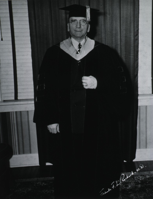<p>Standing, full face, robes and cap.</p>