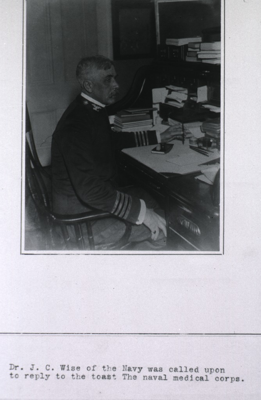 <p>Three-quarter length, right profile, seated at desk.</p>