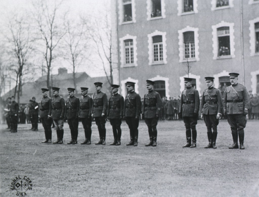 <p>Group of officers about to receive the Distinguished Service Medal; all standing, wearing uniforms and caps; building in background.</p>