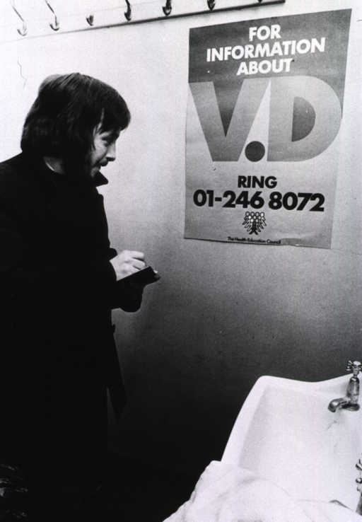 <p>A man is writing down the phone number from a poster about venereal disease which is hanging on a wall in a public bathroom.</p>