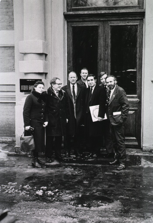 <p>Professors Vera Gerasimova and Anatoly Klimov are standing with Drs. Donald S. Fredrickson, Alexander Nichols, Robert Levy, James Grizzle, and Herman Tyroler.  As part of the US-USSR Cooperative Research Program the group is visiting the lipoprotein laboratory in Leningrad.  They are standing in front of a doorway.  Ice is on the ground.</p>