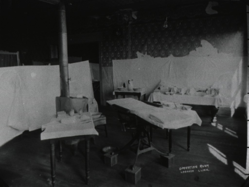 <p>Interior view of room divided by sheets hanging from a rope; an operating table is positioned in the center with smaller instrument tables nearby; a cast-iron stove is behind the tables.</p>