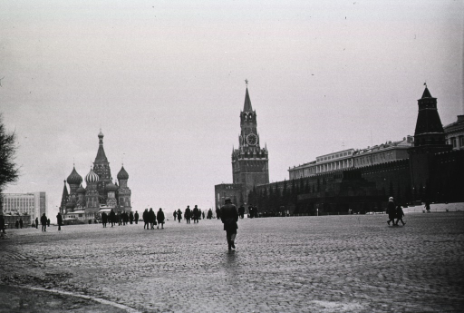 <p>People are walking on the bricked expanse of Red Square.  The St. Basil (Pokrovski) Cathedral and Lenin's Masoleum are in the distance.</p>