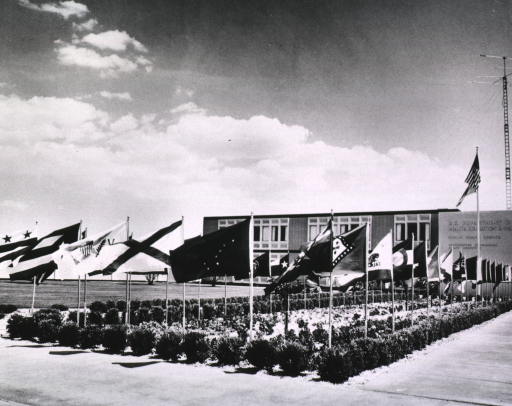 <p>Exterior view showing state flags on short flag poles arranged in a rectangular garden in front of a building.</p>