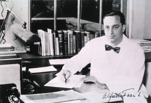<p>Half-length, full face, seated at desk, writing, wearing white coat.</p>