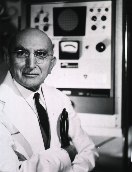 <p>Half-length, right pose, full face; arms folded; wearing white lab coat and glasses; monitoring equipment in background.</p>