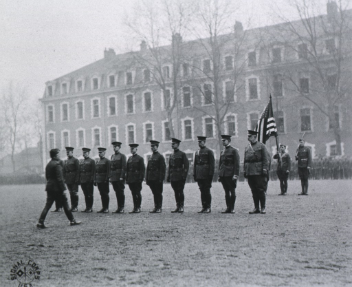 <p>Group of officers to receive the Distinguished Service Medal; all standing, wearing uniforms and caps; building in background.</p>