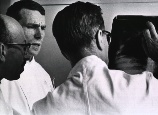 <p>Three physicians are examining x-rays.</p>