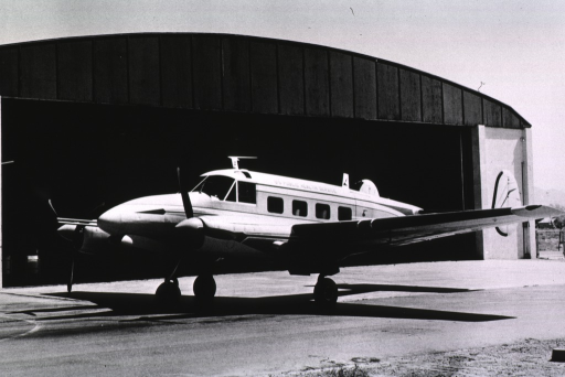 <p>A small (Turbo C-45) airplane in front of a hanger.</p>