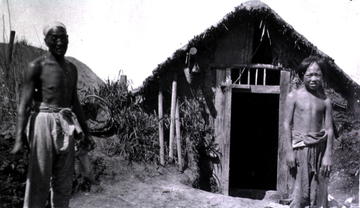 <p>Two Chinese workmen stand near the front entrance of a sod house.</p>