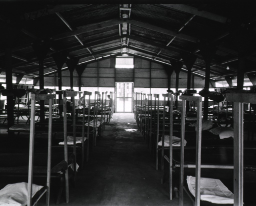 <p>Rows of unoccupied hospital beds are shown in the makeshift structure.</p>