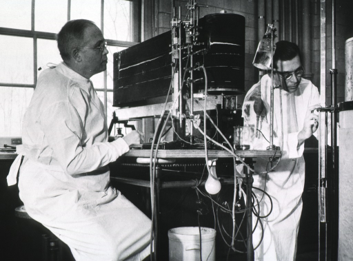 <p>Three-quarters length, seated at moving graph, showing Dr. Dennis D. Donahue to the right.</p>