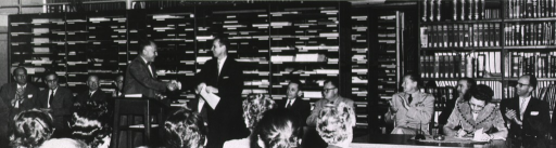 <p>Interior view:  Dr. Edward Cushing presenting book to Dr. Leroy Burney, U. S. Surgeon General, at the ceremony to transfer the Armed Forces Medical Library to the U. S. Public Health Service.</p>