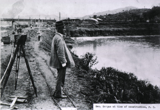 <p>Full length, left profile; wearing coat and hat; on site of Panama Canal.</p>
