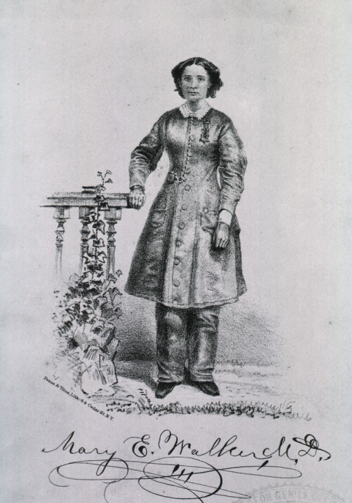 <p>Standing, full length, hand on table.  Wearing trousers and long coat.</p>