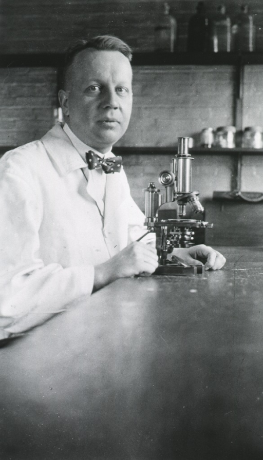 <p>Half length; seated at table, with microscope.  Wearing white coat.</p>