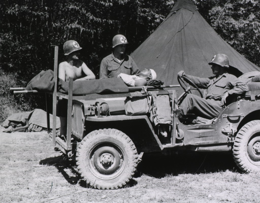 <p>A jeep converted into an ambulance is parked next to a tent.  A serviceman sits at the wheel.  A wounded soldier lies on a litter that is stretched across the hood of the jeep.  Two other servicemen stand next to the wounded soldier.  A forest of trees spreads across the background.  (Cf. no. 33, which is a long-range view of the same subject.)</p>