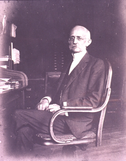 <p>Three-quarter length, seated at desk, left pose, full face; wearing glasses.</p>