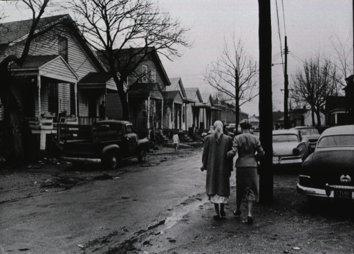 <p>Exterior view: two women walking along a street in a residential area; one of the woman is a volunteer member of the Transportation Corp, and is taking the other woman to a Cancer clinic for treatment.</p>