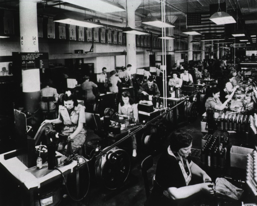 <p>View of a work room at full operation.  Men and women work at various stations.</p>