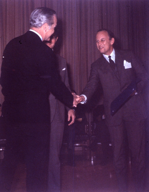 <p>Donald S. Fredrickson, of the National Heart, Lung, and Blood Institute (NHLBI), and Robert Q. Marston, director of the National Institutes of Health (NIH), shake hands.  Dr. Fredrickson is holding an award.  Behind them people are seated in front of a stage curtain.</p>