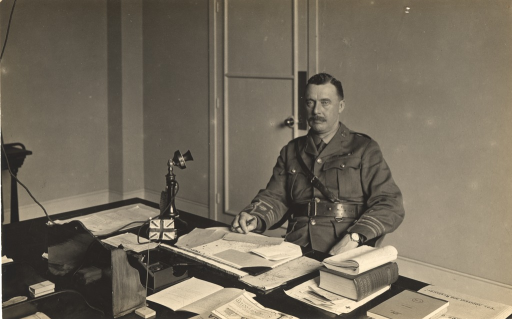 <p>Black and white photograph of Major Parry, adjutant and registrar, sitting at an office desk in King George Military Hospital, London, England.</p>