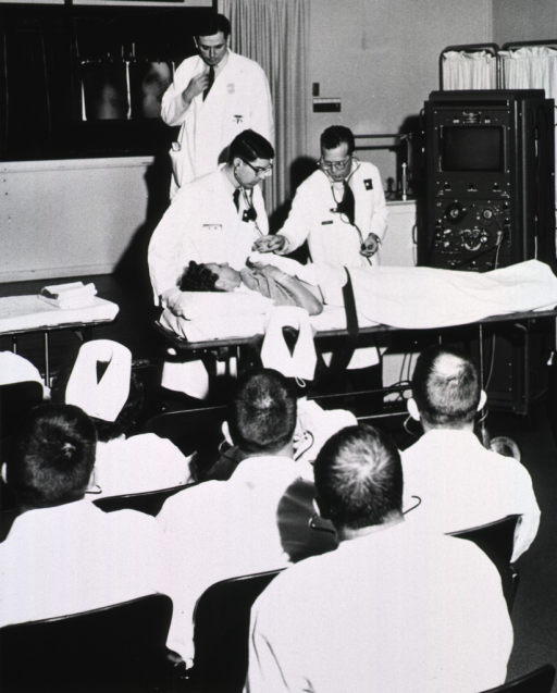 <p>A seated audience of doctors and nurses watches two doctors listen to the heartbeat of a female patient who lies covered on a stretcher.</p>