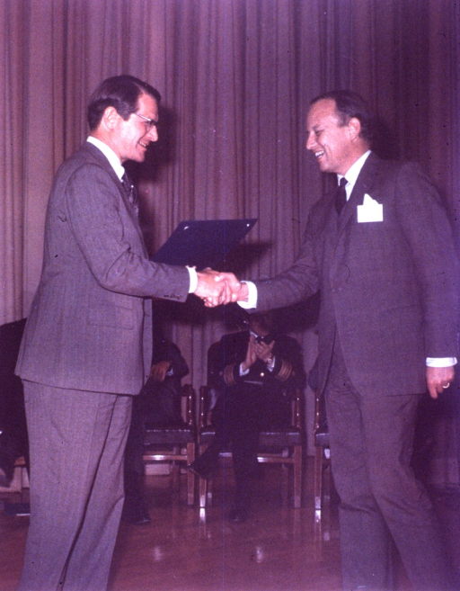 <p>Dr. Donald S. Fredrickson, scientific director of the National Heart, Lung, and Blood Institute (NHLBI), is presented the Distinquished Service Award by Elliot Richardson, secretary of the United States Dept. of Health, Education, and Welfare (DHEW).  Behind them is a man in a uniform applauding.  He is seated with three other people in front of a stage curtain.  Secretary Richardson is holding the award.</p>