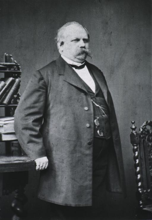 <p>Three-quarter length, standing, right pose, hand on table.</p>