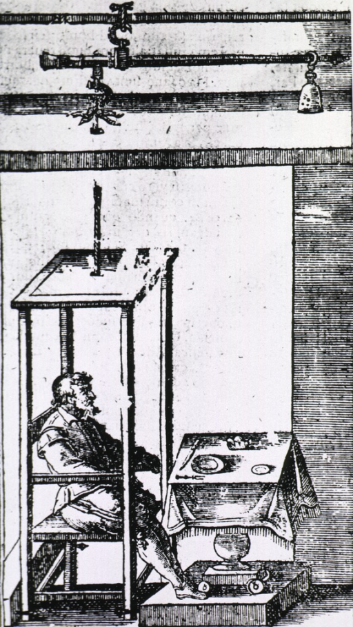 <p>A man sits in a chair which is connected to an apparatus overhead that operates as a large scale; he is seated before a table set for a meal.</p>