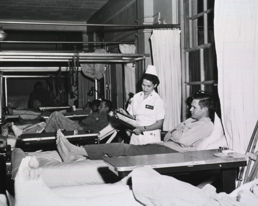 <p>A dietitian stands next to a patient lying on a bed and displays a chart on a clip board.</p>