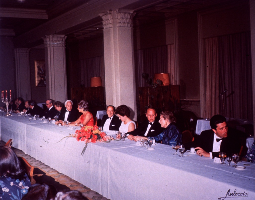 <p>Dr. Donald S. Fredrickson is seated at the head table with 15 other people at the closing dinner of the Jimenez-Diaz ceremonies.  Among the others at the table are Dr. Severo Ochoa and Carmen Ochoa. The dinner is held at the Palace Hotel in Madrid, Spain.  On the table is a candelabra, a flower center piece, wine, water, and champagne glasses, and expresso coffee cups.  There is a microphone behind the table, three curtained windows, two lamp shades, and plants.</p>