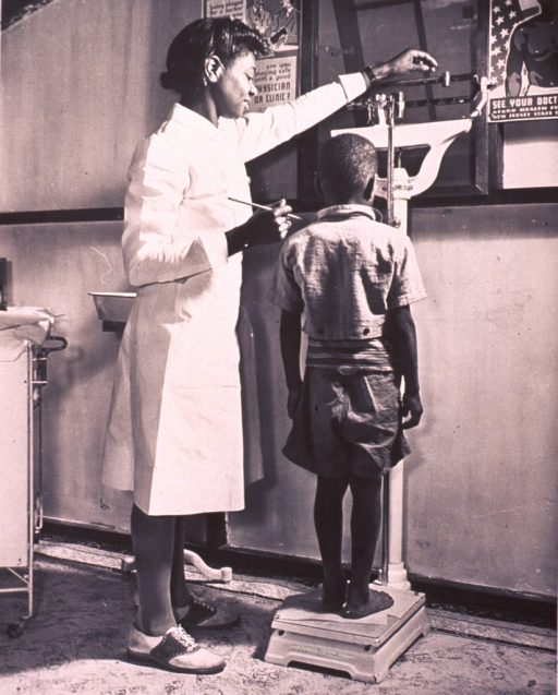 <p>Interior view: an African American child is standing on a scale being weighed by a school nurse.  Two posters about &quot;visiting your physician&quot; are on the wall.</p>
