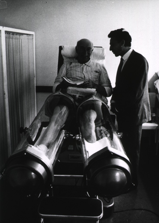<p>Interior view: an old man is sitting in a device that encapsulates each leg for the purpose of stimulating blood circulation; note that his left has been amputated below the knee; a man (physician?) is standing next to him.</p>