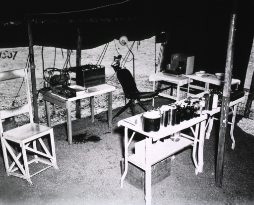 <p>View of the corner of a tent under which are chairs and tables.  On the tables are various equipment and supplies.</p>