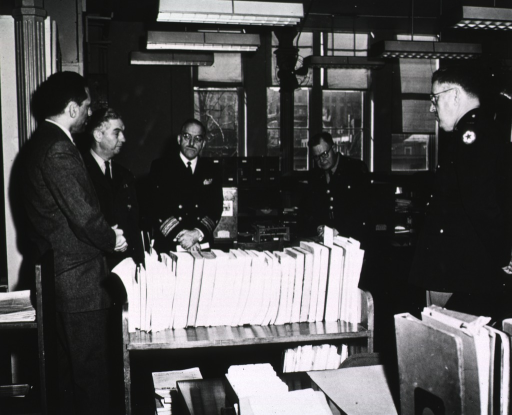 <p>Interior view: Samuel Lazerow, three Surgeons General, and Col. McNinch standing around a book truck of serials.</p>