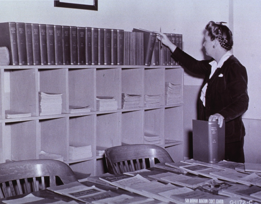 <p>Librarian stands before bookcase of medical bibliographies.</p>