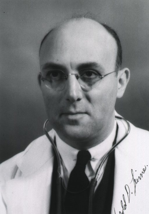 <p>Head and shoulders, left pose, full face; wearing white coat and glasses; stethoscope around neck.</p>