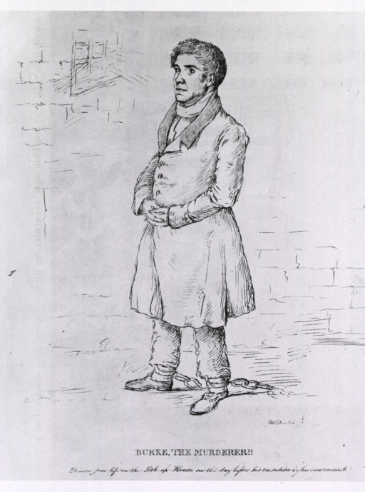 <p>Full length view of Burke, in a prison cell, wearing leg irons.</p>