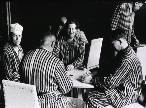 <p>Interior view: a group of men are sitting at a table playing dominoes; they are dressed in hospital garments.</p>