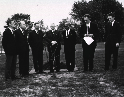 <p>Exterior view:  Planting a cutting from the &quot;Hippocrates&quot; plane tree presented to NLM by the Greek Ambassador, Alexis Liatis, are Mr. Grim, Mr. Kurth, Worth Daniels, Mr. Liekind, Mr. H. Smith, Dr. Rogers and Dr. Blake.  Tree was planted near Library on May 11, 1962.</p>