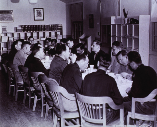 <p>Group of physicians around table in the library reviewing cases and recent medical literature.</p>