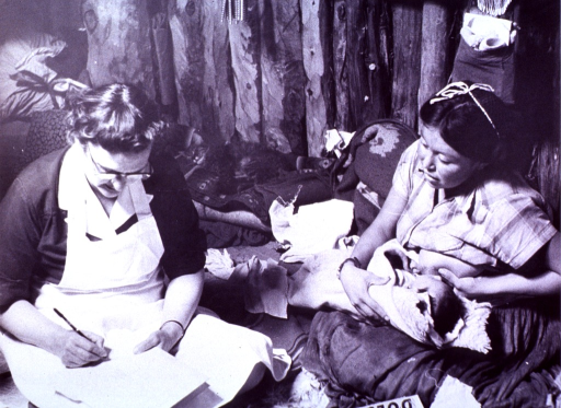 <p>A nurse sits next to a young mother nursing her child; she is filling in forms with the medical history of the woman and her child.</p>