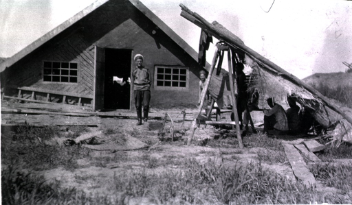 <p>A front view of a dugout(?).  A soldier, standing, and a lean-to are in front of the dugout(?).</p>