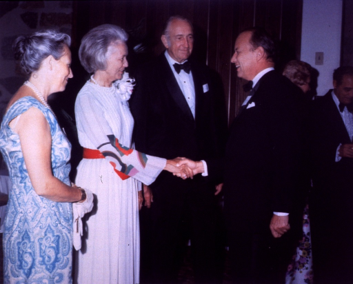 <p>At a black-tie affair, Donald Fredrickson is shaking hands with Lucile Packard.  Mrs. Henriette Fredrickson and David Packard, deputy secretary for defense, are standing with them.  The guests are wearing name tags.  The event celebrates the opening of the Uniformed Services University of the Health Sciences (USUHS).</p>