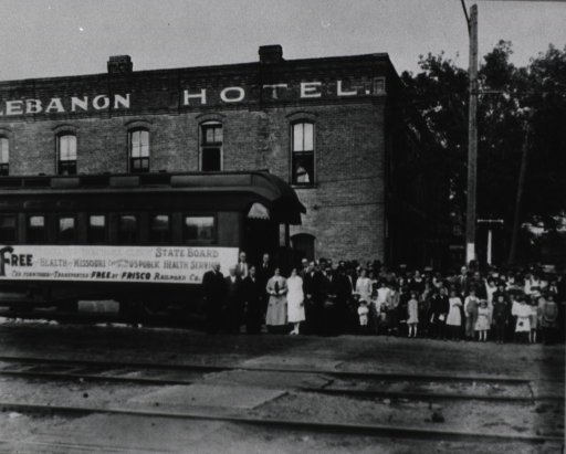 <p>A railroad car furnished as a clinic and transported free by the St. Louis &amp; San Francisco Railroad Co. sits in outside the Lebanon Hotel; clinic staff, local officials, and a crowd of citizens stand at the end of the railroad car.</p>